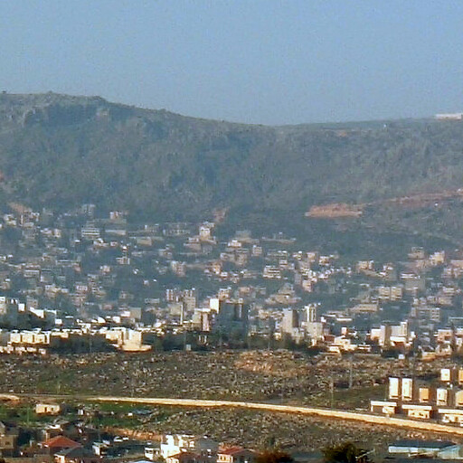 cityscape of Bi'ina, which is behind the buildings on the hill in the foreground